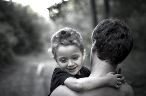 A black and white photo in which a small child smiles towards the viewer in the arms of a man facing away from the camera and down a path that curves into the blurry distance.