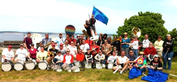 Large group photo of the Rainbow City Gay Band-- with over 80 members sitting on a lawy with their instruments.